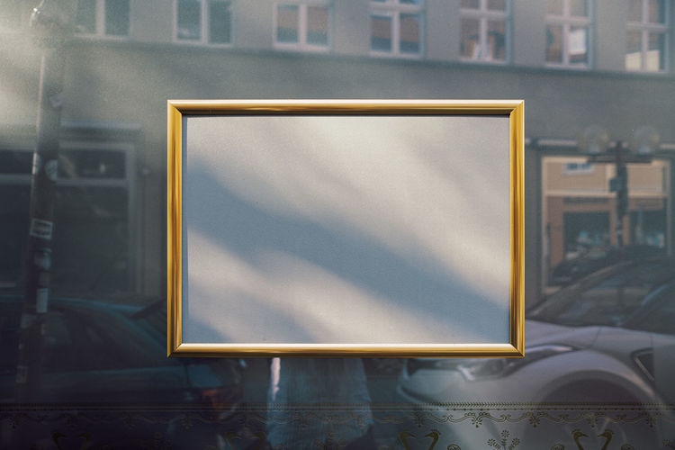 Empty golden picture frame on window