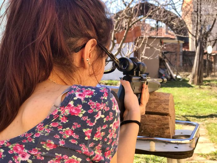 Rear View Of Young Woman Shooting Weapon At Backyard