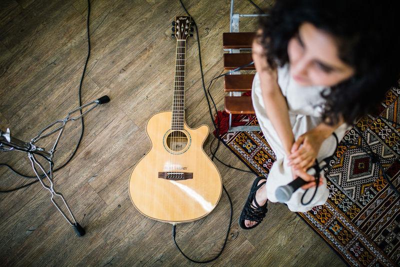 Man playing guitar on hardwood floor