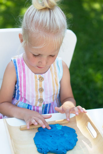 Full length of cute girl sitting outdoors