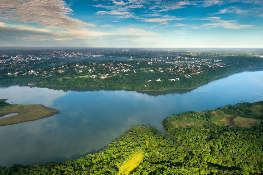 Aerial view of Parana River on the border of Paraguay and Brazil and ciudad del este Brazil City Ciudad Del Este Green Houses Nature Paraná Paraná River Aerial Aerial View Border Day Jungle Landscape Nature Paraguay River Scenics - Nature Suburbs Tranquility