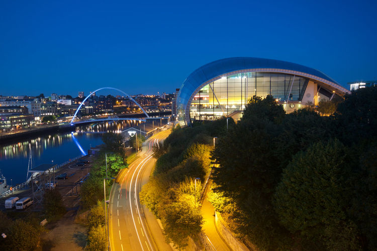 Taken at dusk from the Tyne Bridge looking down river, the Sage Centre and Millennium Bridges span the Tyne to join Newcastle and Gateshead in North East England. Architecture Gateshead Gateshead Millenium Bridge Newcastle Upon Tyne Sage Building Exterior Dusk Sage Centre Street Lights