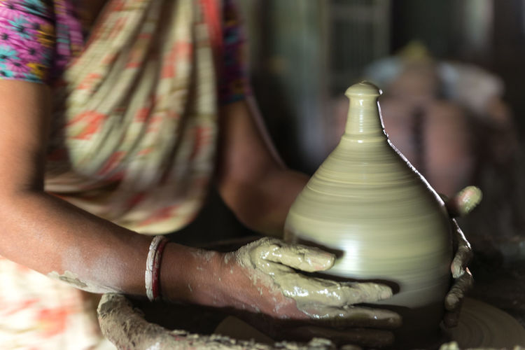 Midsection Of Woman Making Pottery