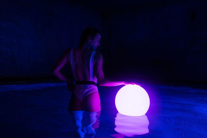 Woman standing against illuminated light
