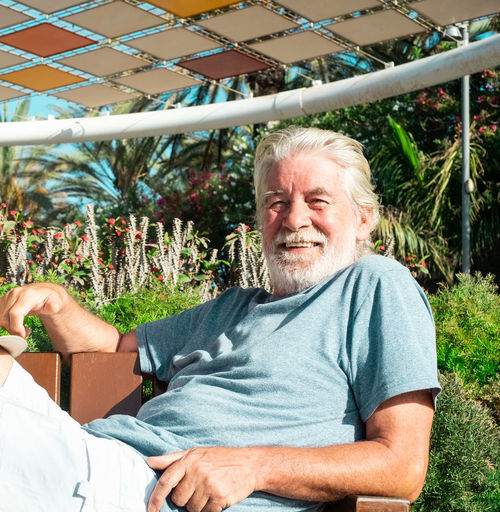 Portrait of smiling senior man relaxing on bench during sunny day
