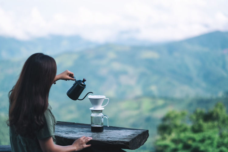 Woman drinking water from coffee in mountains