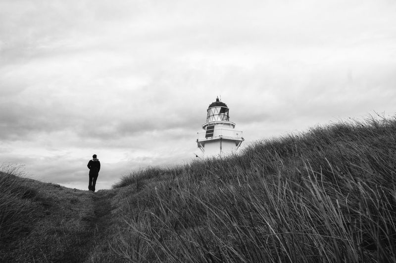 Low Angle View Of Person Walking On Field By Waipapa Point Lighthouse Against Sky