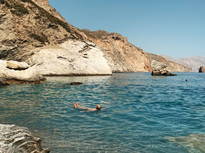 Amorgos Landscape Travel Destinations Tranquil Scene Sea Ocean Water Waterfront Nature Clear Sky Day Beauty In Nature Outdoors Real People Mountain Rock - Object One Person Leisure Activity Scenics Vacations Lifestyles Full Length Swimming Sky People