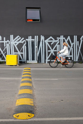 Yellow square. Part two. - Sometimes patience pays off. Very happy the bike entered the scene. The orange color resonates well with the object behind the window. Eye4photography  EyeEm Gallery Eyem Best Shots Streetphotography Mobility Day Yellow Mode Of Transportation Road Marking Transportation Lifestyle City Woman Cyclist Cycling Bicycle Road Simplicity Black And Yellow  Yellow And Orange Geometric Shape Speed Bump