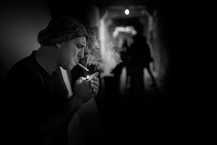 Side view of man smoking cigarette in corridor