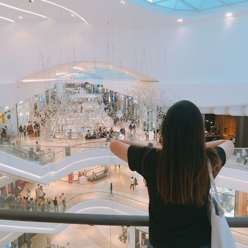 Rear View Of Young Woman Standing In Shopping Mall