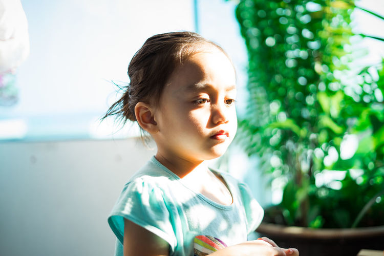Outdoor portrait of an asian little kid under the sunlight on her face.