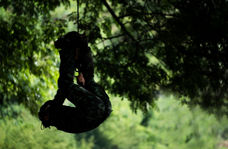 Soldier rappel down or soldier down the rope spiderman Tree Plant Nature Outdoors Day One Person Focus On Foreground Real People Full Length Men Rear View Lifestyles Mid-air Silhouette Sport Leisure Activity Vitality Motion Emotion Soldier Military