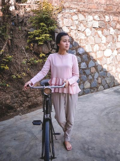 Portrait of woman with bicycle standing against wall