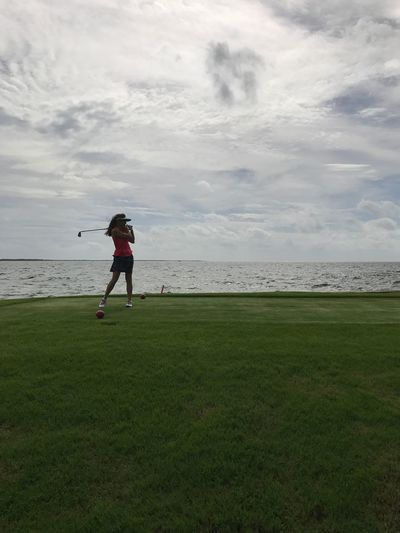 Woman playing golf on grassy field by sea against cloudy sky