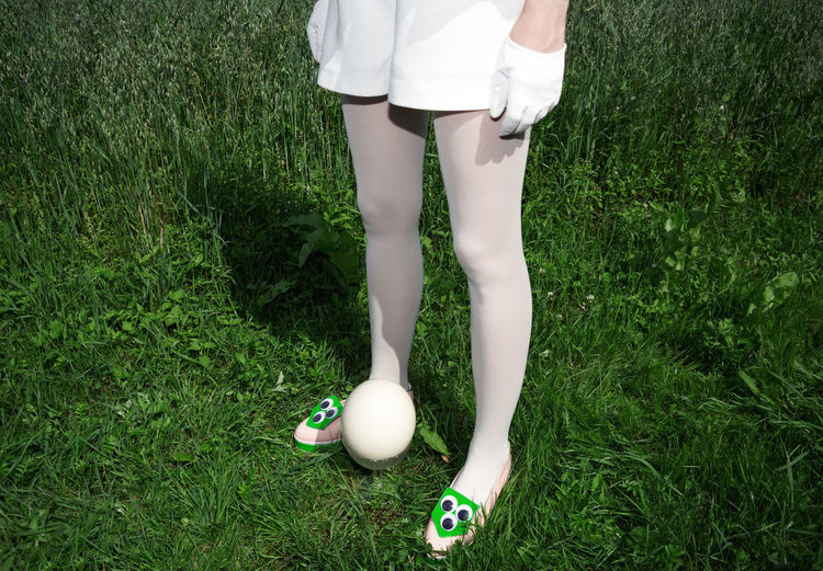 Low section of woman standing by easter egg on field
