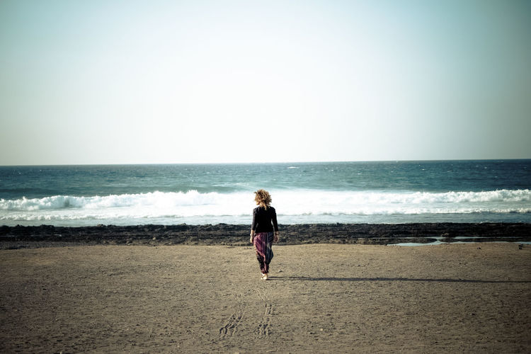 Woman standing at beach against clear sky