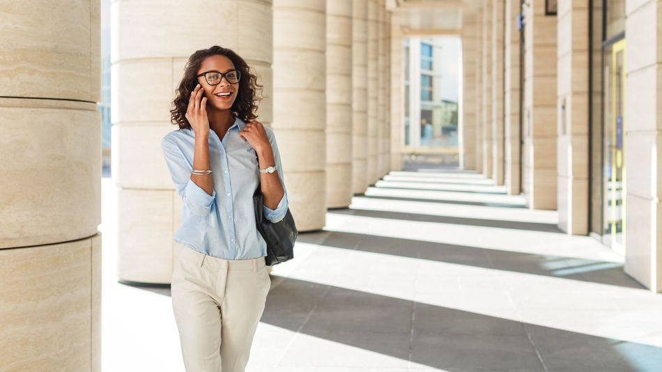 Looking At Camera Portrait Architecture One Person Standing Front View Glasses Eyeglasses  Hairstyle Business Person Smiling Mobile Phone Cell Phone  Walking City Outdoors Real People African American Communication Conversation Entrepreneur Young