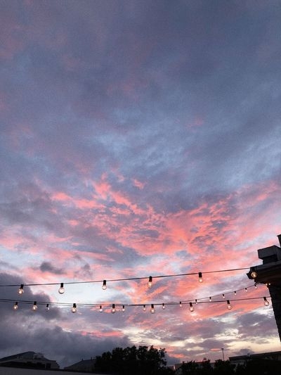 Low angle view of illuminated light bulbs against dramatic sky during sunset