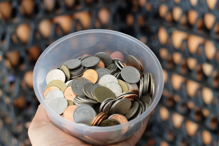 Cropped hand holding coins in container