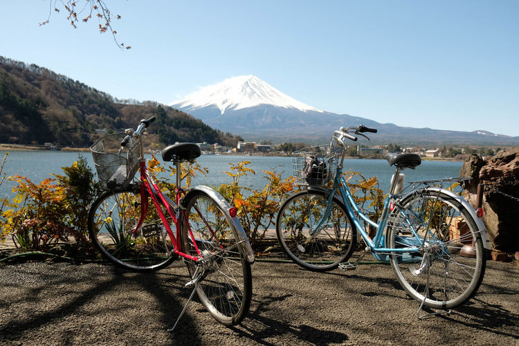 Bicycles on street by lake against sky