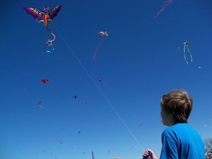 EyeEmNewHerе Kite Blue Blue Sky Boys Childhood Clear Sky Day Enjoyment Flying Fun Kite Kite - Toy Leisure Activity Lifestyles Low Angle View Mid-air Nature One Person Outdoors People Real People Sky