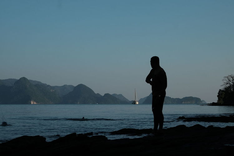 Silhouette Man Standing By Lake Against Clear Sky