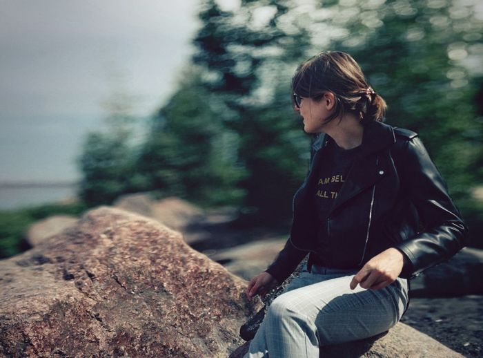 Woman sitting on rock looking away