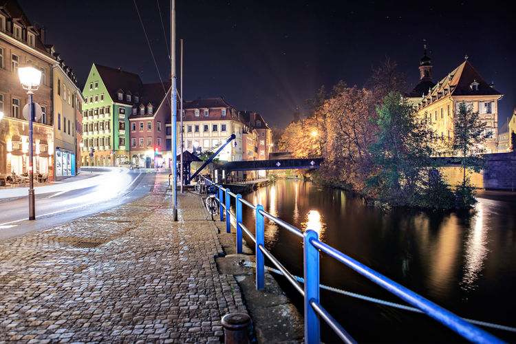 Canal By Illuminated Buildings In City At Night