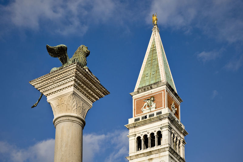 Low angle view of monument and san marco campanile against blue sky