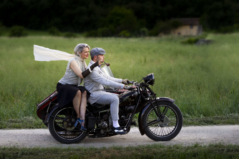 Side view of people riding motorcycle