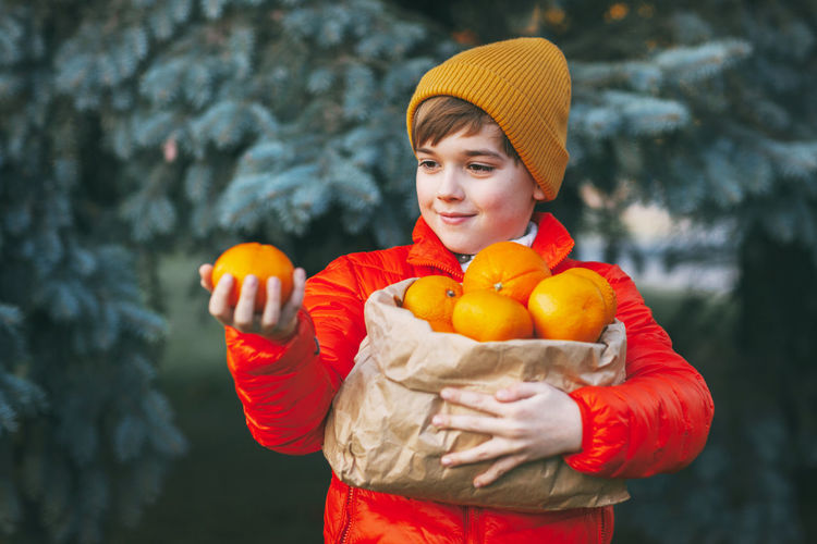 A boy in a bright orange jacket and yellow hat holds a large bag of oranges in his hands