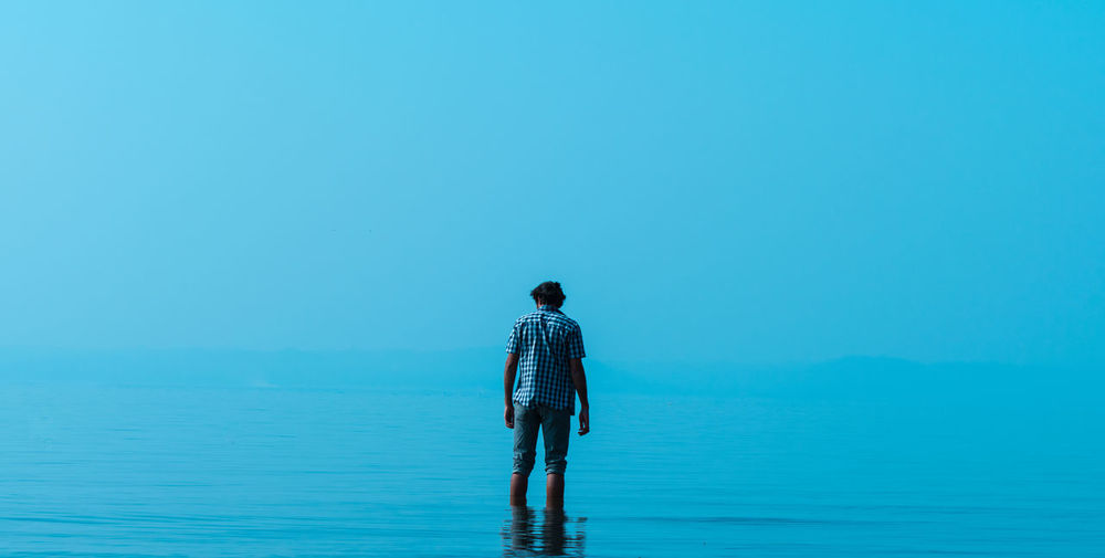 Rear View Of Man In Shallow Water Against Blue Sky