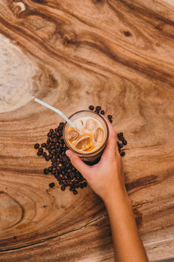 ice coffee Wood Material Coffee Bean Milk Textured  Coffee Ice Coffee Human Hand Time Close-up Roasted Coffee Bean Frothy Drink Caffeine Raw Coffee Bean