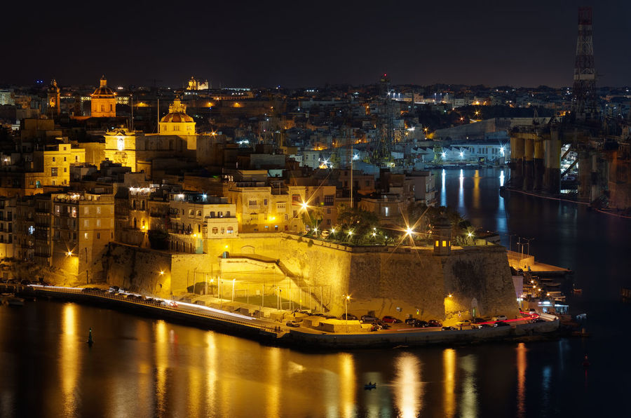 View at Grand Harbor from Upper Barrakka Gardens at night. Valletta city, European island state of Malta Grand Harbour Limestone Wall - Building Feature Building Exterior Illuminated Architecture Night Water City Built Structure Reflection Building Cityscape Nature No People Travel Destinations Residential District River High Angle View Sky Outdoors Long Exposure Limestone Grand Harbour Malta Reflection Human Settlement TOWNSCAPE Urban Scene Residential Structure