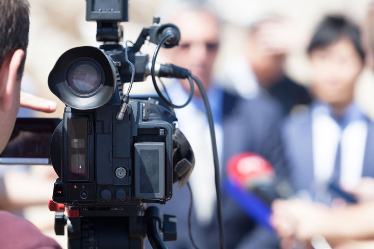 Journalist video recording business people