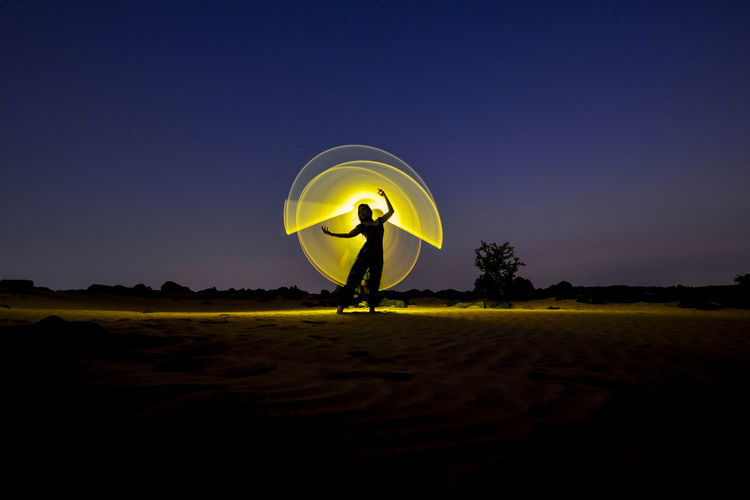 Silhouette person standing on field against clear sky at night