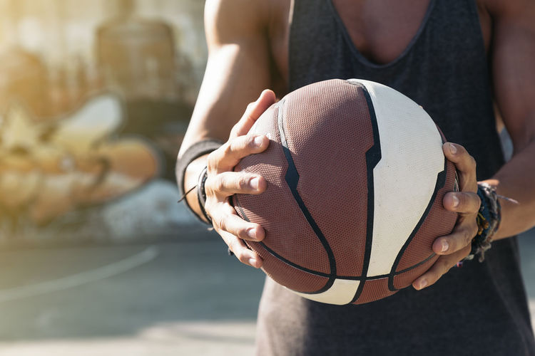 Midsection of man holding basketball