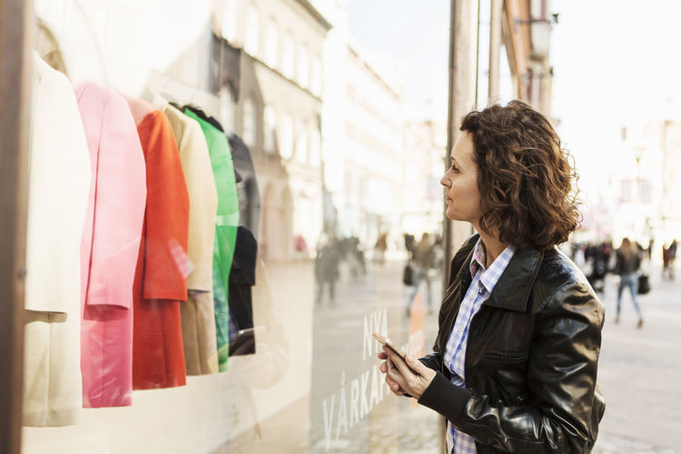 Side view of woman using mobile phone in city