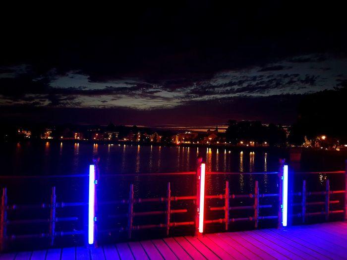 Illuminated city by lake against sky at night