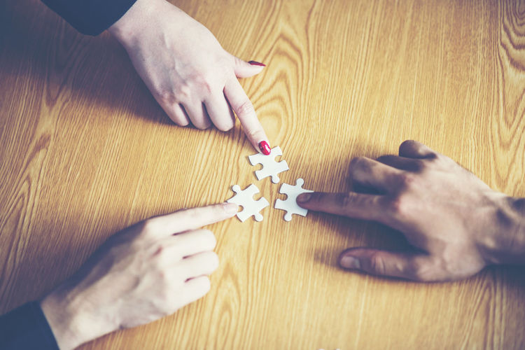 Cropped Hands Of Business Colleagues Playing Jigsaw Puzzle At Desk In Office