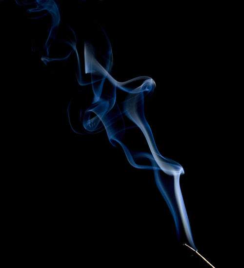 Incense stick emitting smoke against black background