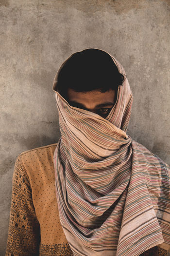 Portrait of man face covered with towel against wall