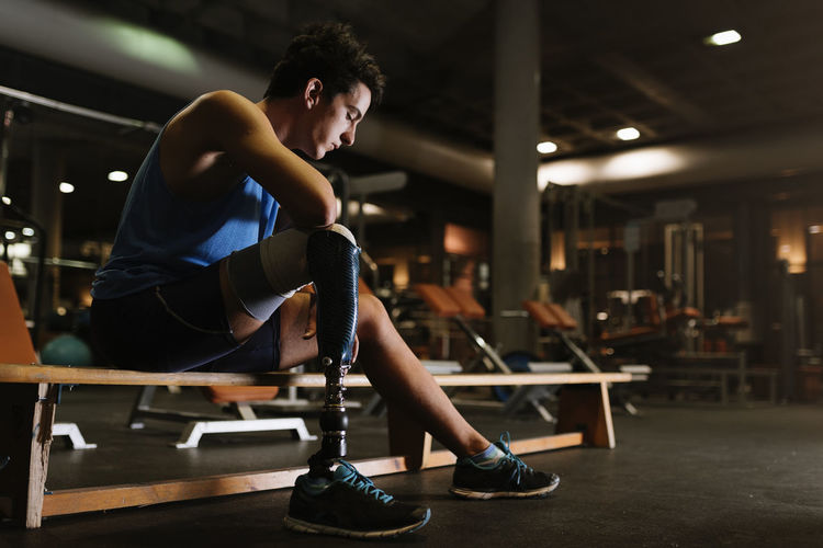 Full length of young man with prosthetic leg sitting on bench in gym