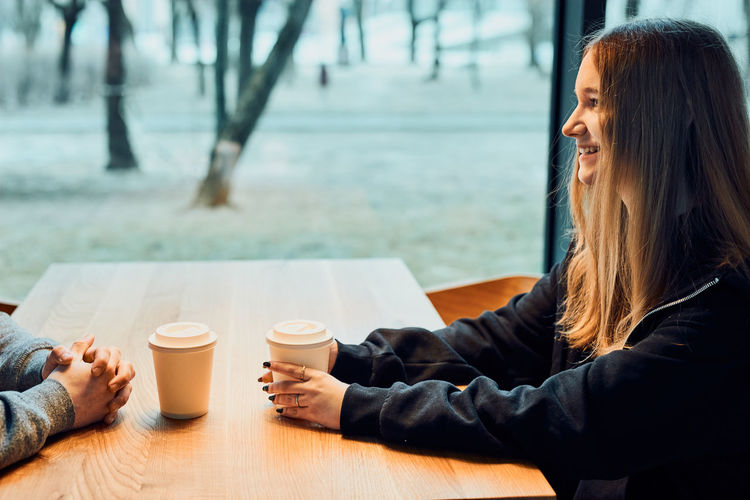 Midsection of woman with coffee cup on table