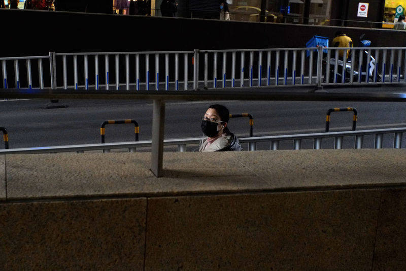 Portrait of woman sitting on railing at night