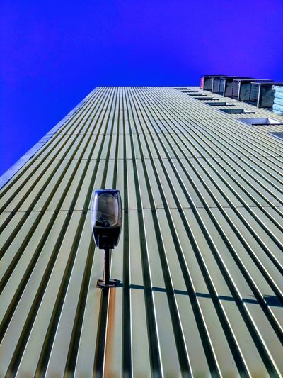 The wall, with lamp and corrosion Pattern No Clouds Clear Sky Lamp Wall Yellow City Clear Sky Roof Blue Sky Architecture Built Structure Skyscraper Cityscape Residential District Urban Skyline The Street Photographer - 2018 EyeEm Awards