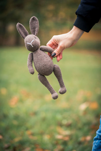 Cropped hand of woman holding stuffed toy outdoors