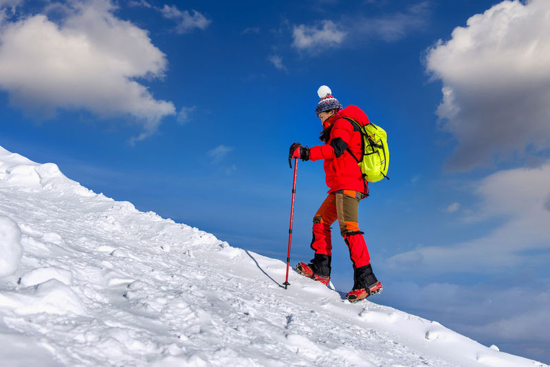 Side View Of Female Hiker Walking On Snow Covered Field Against Sky