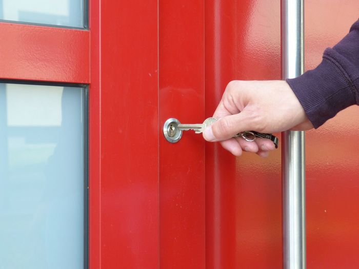Cropped hand of person holding key over hole on closed red door